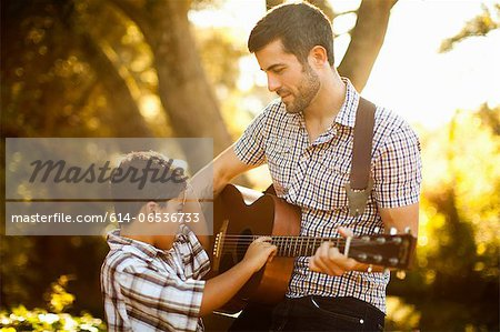 Father and son playing guitar together Stock Photo - Premium Royalty-Free, Image code: 614-06536733