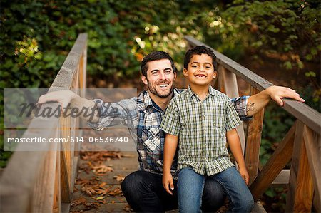 Father and son playing on wooden bridge Stock Photo - Premium Royalty-Free, Image code: 614-06536740