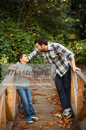 Father and son playing on wooden bridge Stock Photo - Premium Royalty-Free, Image code: 614-06536742