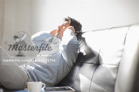Man listening to headphones on sofa Stock Photo - Premium Royalty-Free, Image code: 614-06536756
