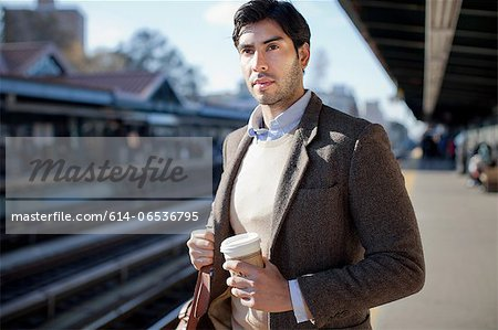 Man with cup of coffee at train station Stock Photo - Premium Royalty-Free, Image code: 614-06536795