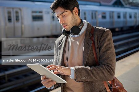 Man using tablet computer at station Stock Photo - Premium Royalty-Free, Image code: 614-06536797