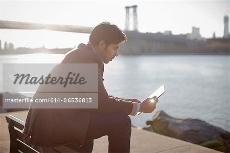 Man using tablet computer outdoors Stock Photo - Premium Royalty-Free, Image code: 614-06536813