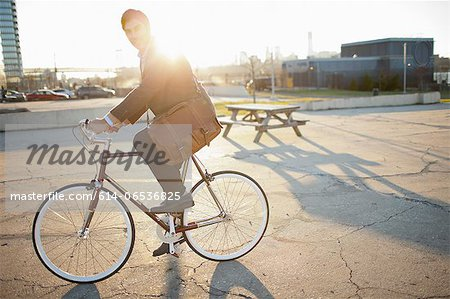 Man riding bicycle on city street Stock Photo - Premium Royalty-Free, Image code: 614-06536825