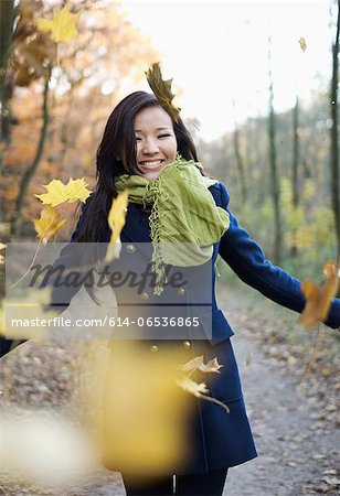 Woman playing in autumn leaves Stock Photo - Premium Royalty-Free, Image code: 614-06536865