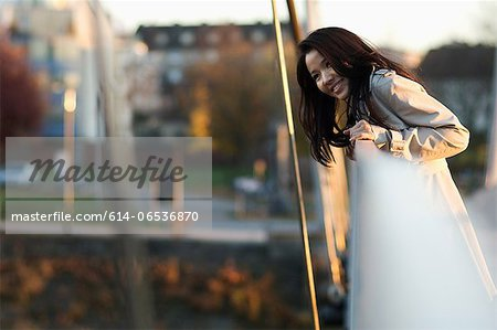 Woman leaning over bridge railing Stock Photo - Premium Royalty-Free, Image code: 614-06536870