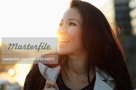 Smiling woman standing outdoors Stock Photo - Premium Royalty-Free, Image code: 614-06536872