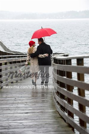Couple walking on wooden pier in rain Stock Photo - Premium Royalty-Free, Image code: 614-06536900