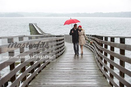 Couple walking on wooden pier in rain Stock Photo - Premium Royalty-Free, Image code: 614-06536902