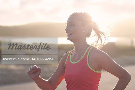Woman running on beach Stock Photo - Premium Royalty-Free, Image code: 614-06536958