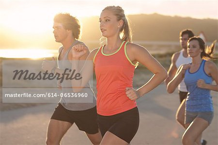 Friends running on beach Stock Photo - Premium Royalty-Free, Image code: 614-06536960