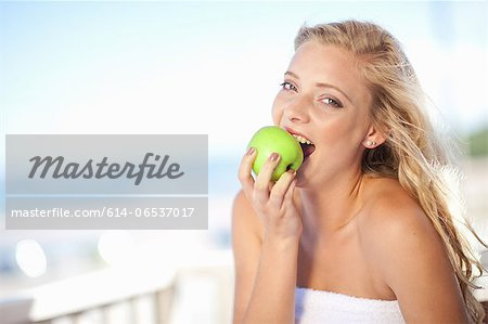 Woman eating apple outdoors Stock Photo - Premium Royalty-Free, Image code: 614-06537017
