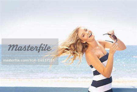 Woman tossing her hair on beach Stock Photo - Premium Royalty-Free, Image code: 614-06537101