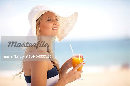 Woman in floppy hat having juice Stock Photo - Premium Royalty-Free, Image code: 614-06537110