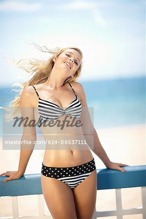 Woman in bikini standing on deck Stock Photo - Premium Royalty-Free, Image code: 614-06537111