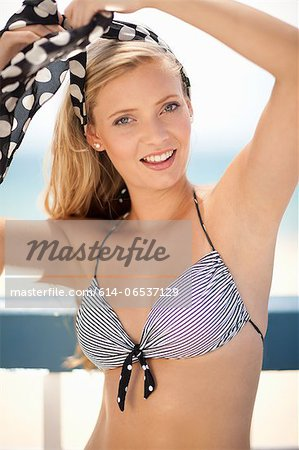 Smiling woman tying scarf in hair Stock Photo - Premium Royalty-Free, Image code: 614-06537129