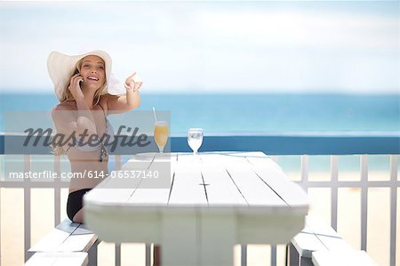 Woman on cell phone at table on deck Stock Photo - Premium Royalty-Free, Image code: 614-06537140