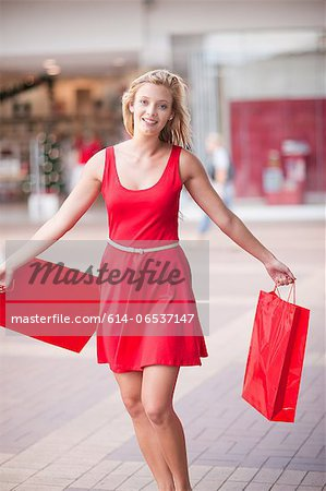 Woman carrying shopping bags in mall Stock Photo - Premium Royalty-Free, Image code: 614-06537147