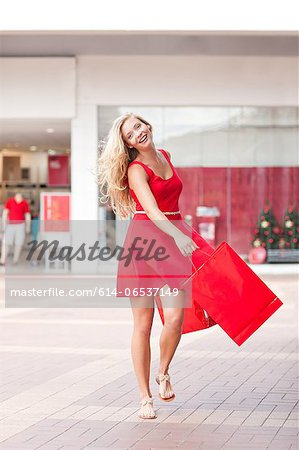 Woman carrying shopping bags in mall Stock Photo - Premium Royalty-Free, Image code: 614-06537149