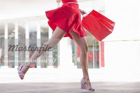 Woman carrying shopping bag outdoors Stock Photo - Premium Royalty-Free, Image code: 614-06537162