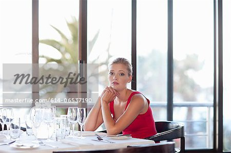 Woman sitting at restaurant table Stock Photo - Premium Royalty-Free, Image code: 614-06537190