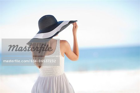 Woman wearing floppy hat on beach Stock Photo - Premium Royalty-Free, Image code: 614-06537232