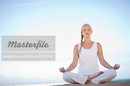 Woman meditating on beach Stock Photo - Premium Royalty-Free, Image code: 614-06537234
