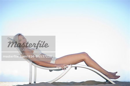 Woman relaxing in lawn chair on beach Stock Photo - Premium Royalty-Free, Image code: 614-06537236