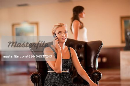 Woman talking on cell phone in lobby Stock Photo - Premium Royalty-Free, Image code: 614-06537243