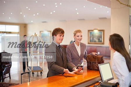 Businesswoman checking in to hotel Stock Photo - Premium Royalty-Free, Image code: 614-06537250