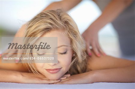 Smiling woman having massage Stock Photo - Premium Royalty-Free, Image code: 614-06537320
