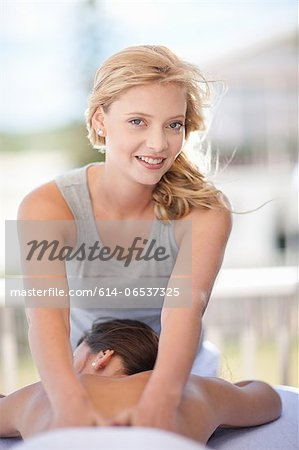 Smiling woman giving massage outdoors Stock Photo - Premium Royalty-Free, Image code: 614-06537325