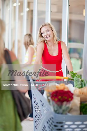 Women pushing shopping cart Stock Photo - Premium Royalty-Free, Image code: 614-06537358