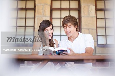 Couple reading travel book together Stock Photo - Premium Royalty-Free, Image code: 614-06537382