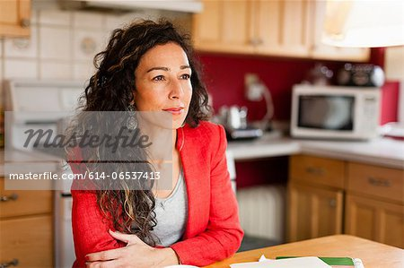 Smiling woman sitting in kitchen Stock Photo - Premium Royalty-Free, Image code: 614-06537413