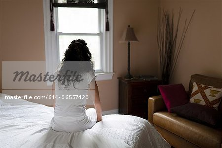 Woman sitting on edge of bed Stock Photo - Premium Royalty-Free, Image code: 614-06537420