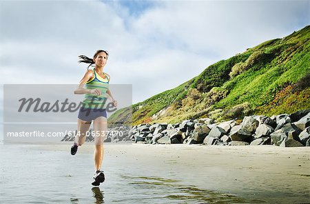 Woman running on beach Stock Photo - Premium Royalty-Free, Image code: 614-06537470