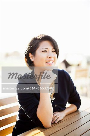 Smiling woman sitting at picnic table Stock Photo - Premium Royalty-Free, Image code: 614-06537503