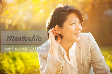 Smiling businesswoman sitting outdoors Stock Photo - Premium Royalty-Free, Image code: 614-06537504