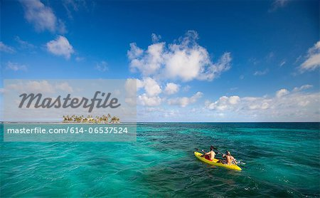 People rowing canoe in tropical water Stock Photo - Premium Royalty-Free, Image code: 614-06537524