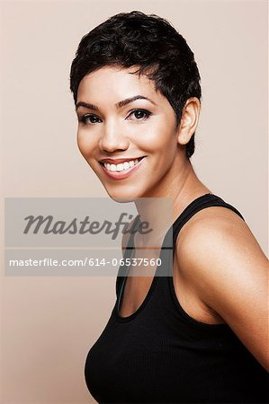 Smiling woman standing indoors Stock Photo - Premium Royalty-Free, Image code: 614-06537560