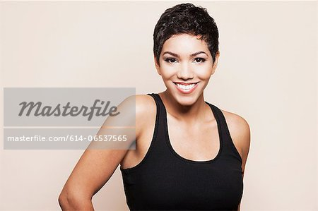 Smiling woman standing indoors Stock Photo - Premium Royalty-Free, Image code: 614-06537565