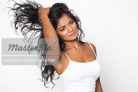 Smiling woman tossing her hair Stock Photo - Premium Royalty-Free, Image code: 614-06537580