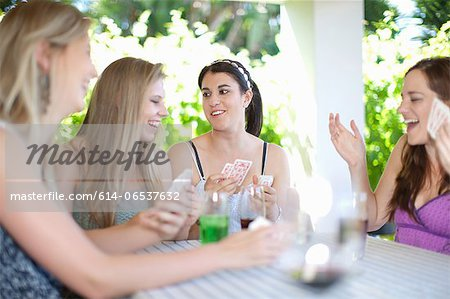 Women playing cards at table Stock Photo - Premium Royalty-Free, Image code: 614-06537632