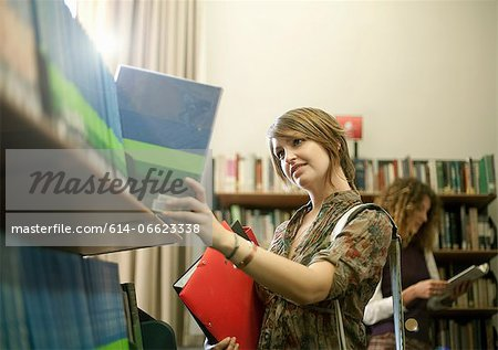 Student searching for book in library Stock Photo - Premium Royalty-Free, Image code: 614-06623338