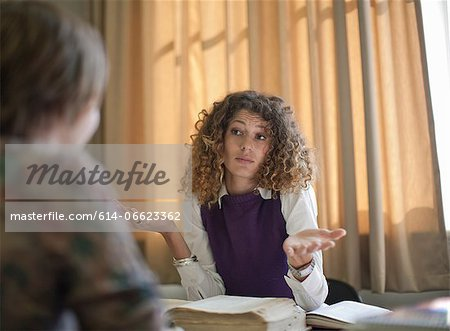 Student shrugging at desk Stock Photo - Premium Royalty-Free, Image code: 614-06623362