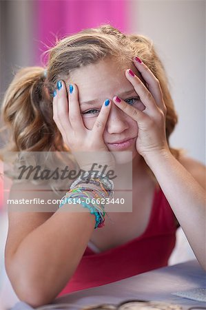 Frustrated girl with head in hands Stock Photo - Premium Royalty-Free, Image code: 614-06623440