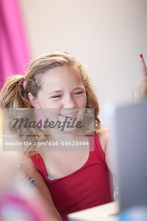 Smiling girl using laptop Stock Photo - Premium Royalty-Free, Image code: 614-06623444