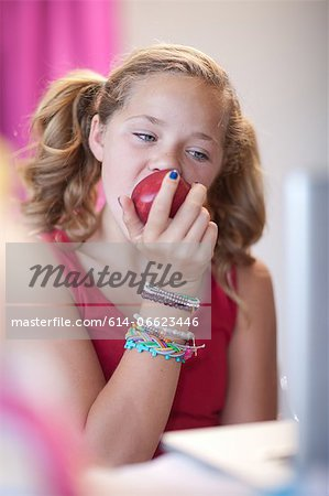 Girl eating apple at desk Stock Photo - Premium Royalty-Free, Image code: 614-06623446