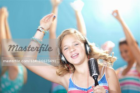 Girl singing into hairbrush Stock Photo - Premium Royalty-Free, Image code: 614-06623491
